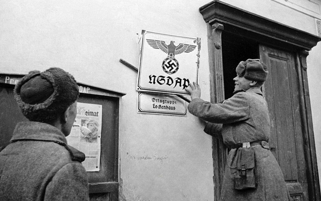 Красноармейцы сбивают табличку на здании местной группы НСДАП во взятом Локенхаузе (Lockenhaus)