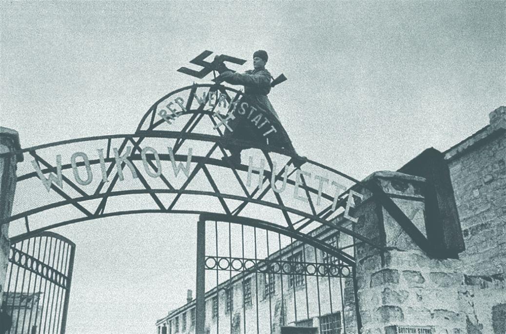 Советский солдат срывает нацистскую свастику с ворот металлургического завода им. Войков